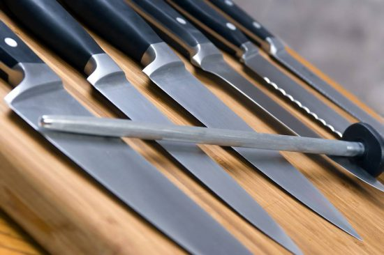 Close-up of kitchen knives on a wooden cutting board